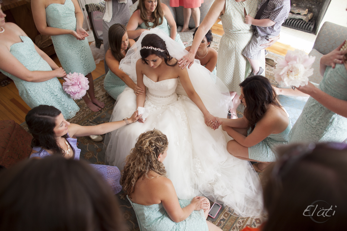 Bride praying with bride's maids